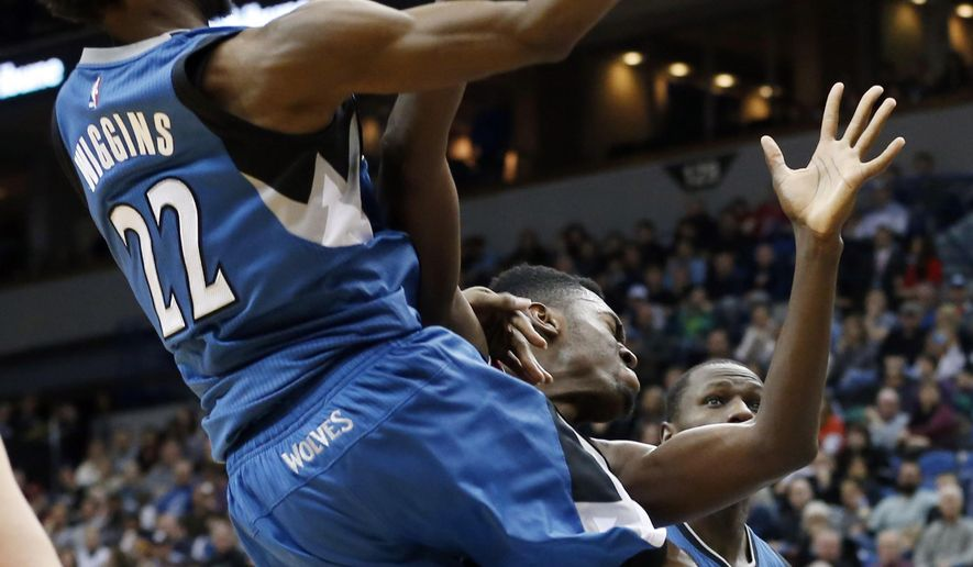 Minnesota Timberwolves' Andrew Wiggins, left, lays up a shot as he collides with Chicago Bulls' Bobby Portis in the second half of an NBA basketball game, Saturday, Feb. 6, 2016, in Minneapolis. The Timberwolves won 112-105. Wiggins scored 21 points. (AP Photo/Jim Mone)