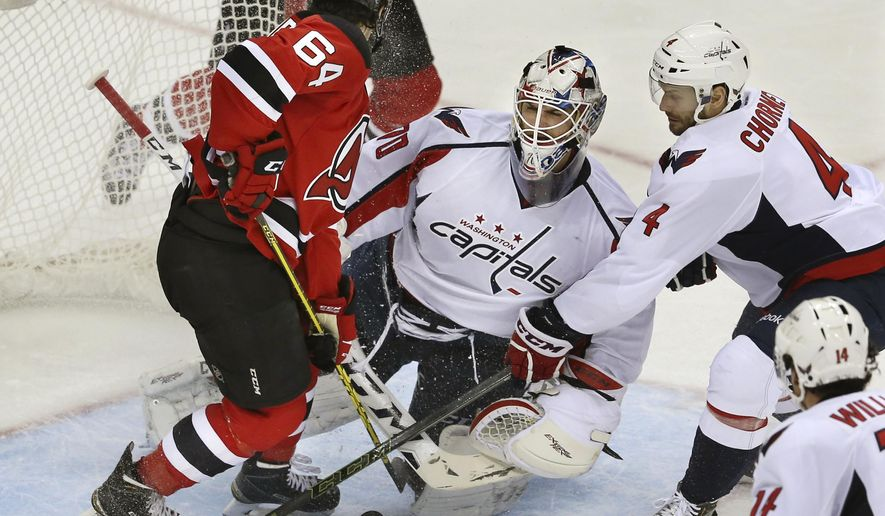 Washington Capitals defenseman Taylor Chorney (4) tries to help out goalie Braden Holtby (70) as New Jersey Devils center Joseph Blandisi (64) tries to score during the second period of an NHL hockey game Saturday, Feb. 6, 2016, in Newark, N.J. (AP Photo/Mel Evans)