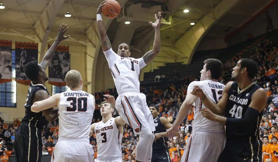 Oregon State's Gary Payton II, center, grabs a rebound in the first half of an NCAA college basketball game in Corvallis, Ore., on Saturday, Feb. 6, 2016. (AP Photo/Timothy J. Gonzalez)