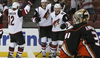 Arizona Coyotes' Brad Richardson (12), Jarred Tinordi, and Tobias Rieder (8) celebrate Rieders' goal as Anaheim Ducks goalie Frederik Andersen (31) looks away in the first period of an NHL hockey game in Anaheim, Calif., Friday, Feb. 5, 2016. (AP Photo/Christine Cotter)