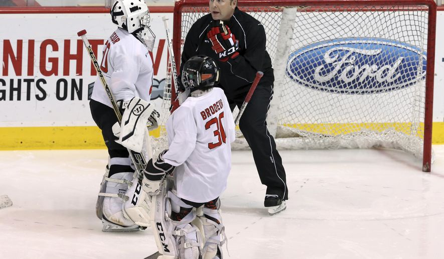 Children wearing Martin Brodeur jerseys listen, as the former New Jersey Devils goalie Martin Brodeur gives them pointers during a hockey camp before an NHL hockey game between the Devils and Washington Capitals Saturday, Feb. 6, 2016, in Newark, N.J. (AP Photo/Mel Evans)
