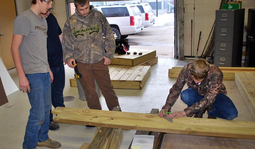 Students involved in SkillsUSA measure wooden beams they are using to make handicap ramps on Jan. 27, 2016 in Freemont, Neb.  While SkillsUSA is designed to build real-world job skills that enable students to immediately make an impact in the trades job market, one of the biggest factors involves service in the community.  (Sam Pimper /The Tribune via AP) MANDATORY CREDIT