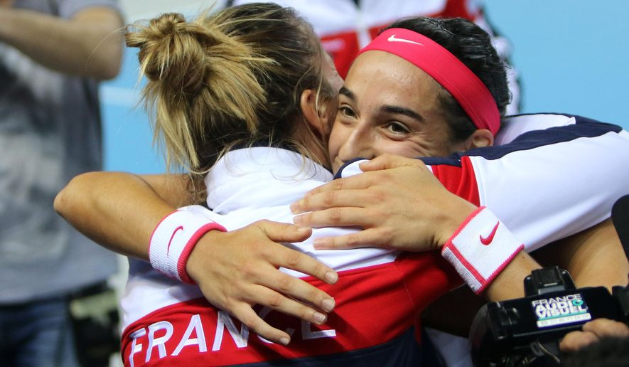 France's Caroline Garcia, right, celebrates with her teammate Pauline Parmentier, her victory after defeating Italy's Sara Errani during the first round of the Fed Cup competition between France and Italy, in Marseille, southern France, Saturday, Feb. 6, 2016. (AP Photo/Claude Paris)