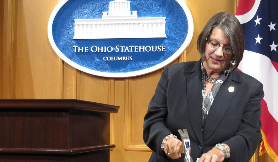 FILE - In this Sept. 17, 2015 file photo, Ohio state Rep. Nickie Antonio, a Democrat from Lakewood in suburban Cleveland, demonstrates tamper-resistant pain pills by unsuccessfully attempting to pulverize them with a hammer, during a news conference in Columbus, Ohio. Antonio plans to reintroduce legislation aimed at keeping firearms out of the hands of alleged domestic abusers after a protective order is issued. (AP Photo/Andrew Welsh-Huggins, File)