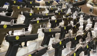 A customer looks at a pistol at a vendor's display at a gun show held by Florida Gun Shows in Miami on Saturday, Jan. 9, 2016. (AP Photo/Lynne Sladky) ** FILE **