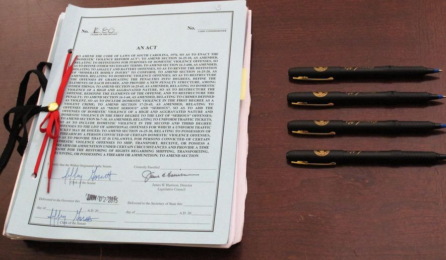 FILE - In this Thursday, June 4, 2015 file photo, pens are placed beside South Carolina's new domestic violence bill before Gov. Nikki Haley signs it into law on in Columbia, S.C. The new law increases penalties for domestic violence and has a gun ban for abusers. (AP Photo/Jeffrey Collins)
