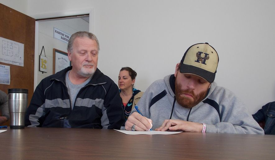 ADVANCE FOR MONDAY FEB. 8 AND THEREAFTER This Monday Feb. 1, 2016 photo shows Shane Unger, right, as he signs papers Tuesday for a new Habitat for Humanity of the Eastern Panhandle home, while his father , Mike, looks on in Martinsburg, W.Va.  (John McVey/The Journal via AP)