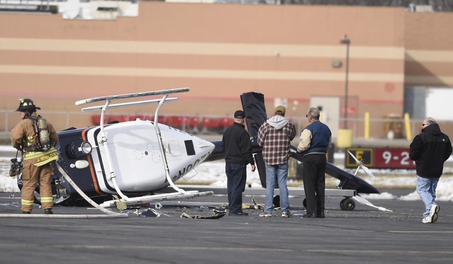 A firefighter and others inspect the wreckage of a helicopter after it crashed at the airport in Linden, N.J., on Saturday, Feb. 6, 2016. Officials say the pilot was making practice landings when it tipped over on its side. (Michael Karas/The Record of Bergen County - Northjersey.com via AP) ONLINE OUT; MAGS OUT; TV OUT; INTERNET OUT;  NO ARCHIVING; MANDATORY CREDIT