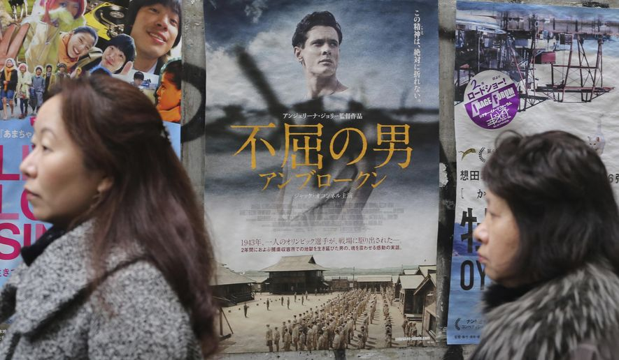 """Moviegoers wait before Angelina Jolie's """"Unbroken"""" opens in front of a movie theater in Tokyo, Saturday, Feb. 6, 2016. """"Unbroken"""" has opened more than a year after the rest of the world in Japan, the country where the main character endures as a prisoner of war and where some have called for a boycott of the movie. (AP Photo/Koji Sasahara)"""