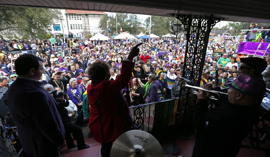 "Grammy Award winning recording artist Irma Thomas, known as the ""soul Queen of New Orleans,"" performs on the front porch of a home on Orleans Ave., as crowds wait for the Krewe of Endymion Mardi Gras parade to pass in New Orleans, Saturday, Feb. 6, 2016. (AP Photo/Gerald Herbert)"