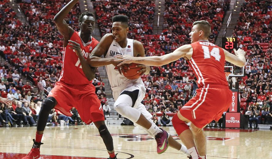 San Diego State forward Malik Pope slices through the defense of New Mexico's Dane Kuiper, right, Obij Aget while driving to the basket during the first half of a NCAA college basketball game  Saturday, Feb. 6, 2016, in San Diego. (AP Photo/Lenny Ignelzi)