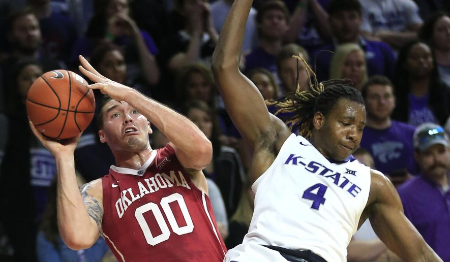 Oklahoma forward Ryan Spangler (00) is fouled by Kansas State forward D.J. Johnson (4) during the first half of an NCAA college basketball game at Bramlage Coliseum in Manhattan, Kan., Saturday, Feb. 6, 2016. (AP Photo/Orlin Wagner)