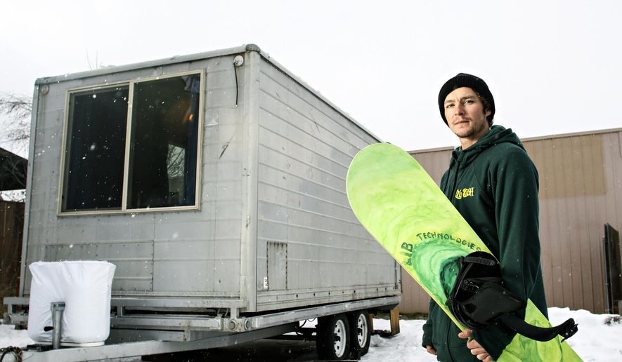 In this photo taken on Jan. 21, 2016, pro snowboarder Jason Robinson poses in front of his small house built on a trailer in Kalispell, Mont.  (Greg Lindstrom/Flathead Beacon via AP) MANDATORY CREDIT