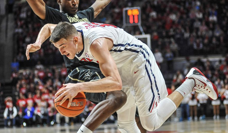 Mississippi forward Tomasz Gielo (12) is fouled by Vanderbilt center Damian Jones during an NCAA college basketball game Saturday, Feb. 6, 2016, in Oxford, Miss. Mississippi won 85-78. (Bruce Newman/Oxford Eagle via AP)