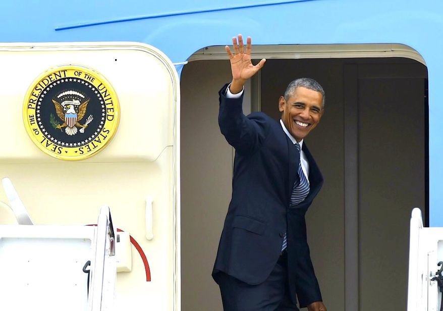 President Obama pauses at the door of Air Force One; he leaves on a weeklong trip to Illinois and the West Coast on Wednesday. (Associated Press)