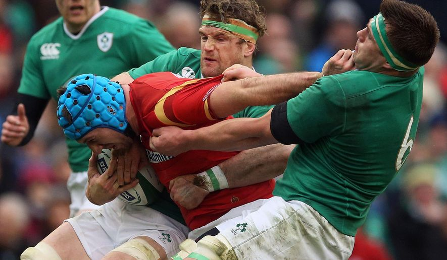 Wales' Justin Tipuric, centre, is tackled by Ireland's CJ Stander, right, and Jamie Heaslip during their 2016 Six Nations rugby match at the Aviva Stadium in Dublin, Sunday Feb. 7, 2016. (Brian Lawless / PA via AP) UNITED KINGDOM OUT - NO SALES - NO ARCHIVES