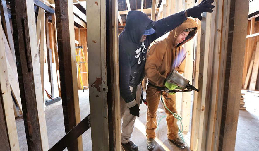 Contractor Linus Onyeneho instructs Quinton Mayle, 17, in the proper use of a nail gun inside a house on Chicago Avenue in Franklinton, Ohio on Jan. 12, 2016. A non-profit called Franklinton Rising is trying to help young people gain job experience while rehabbing houses.  (Chris Russell/The Columbus Dispatch via AP) MANDATORY CREDIT