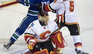 Calgary Flames defenseman Mark Giordano (5) tries to clear Vancouver Canucks right wing Emerson Etem (26) from behind Flames goalie Jonas Hiller (1) during the first period of an NHL hockey game Saturday, Feb. 6, 2016, in Vancouver, British Columbia. (Jonathan Hayward/The Canadian Press via AP)