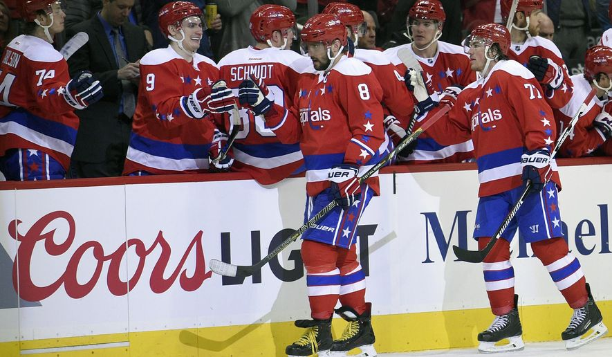 Washington Capitals left wing Alex Ovechkin (8), of Russia, celebrates his goal with teammate Dmitry Orlov (9), also of Russia, and others during the second period of an NHL hockey game against the Philadelphia Flyers, Sunday, Feb. 7, 2016, in Washington. (AP Photo/Nick Wass)