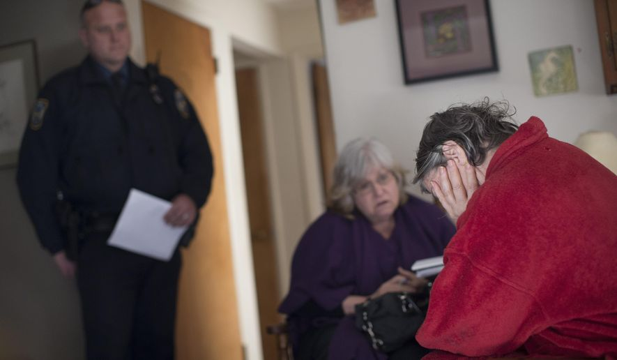 """In this Wednesday, Jan. 6, 2016, photo, Colerain Township Police Det. Dave Hubbard, left, and Nan Franks, CEO of Greater Cincinnati Addiction Services Council, center, meet with a heroin user, who requested to remain anonymous, five days after she nearly died from a heroin overdose in Colerain Township in Hamilton, Ohio. """"I could be dead,"""" the woman, in her 50s, said as Judy Garland's voice warbled poignantly in the living room: """"Somewhere, over the rainbow, way up high."""" (AP Photo/John Minchillo)"""