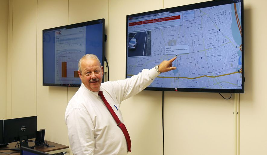 In this Nov. 19, 2015, photo, Freeport Mayor Robert Kennedy demonstrates the village's license plate scanner system at Village Hall in Freeport, N.Y. The new system helped catch a fugitive murder suspect but it also has police spending a lot of time chasing motorists for minor offenses like driving with an expired registration. (AP Photo/Michael Balsamo)