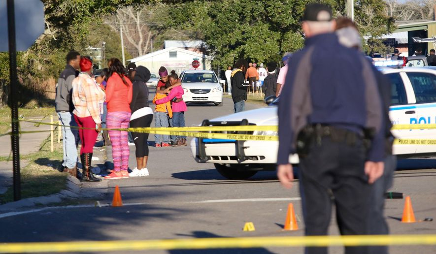 A woman embraces two children near the intersection of Davis Avenue and Ladnier Street in Pass Christian after a shooting on Sunday, Feb. 7, 2016. South Mississippi police say a shooting after a Mardi Gras parade in Pass Christian has left two people dead and four others wounded. (Amanda McCoy/The Sun Herald via AP) /The Sun Herald via AP) LOCAL TELEVISION OUT; MANDATORY CREDIT: MISSISSIPPI PRESS OUT; LOCAL TELEVISION OUT WLOX, LOCAL ONLINE OUT; GULFLIVE.COM OUT