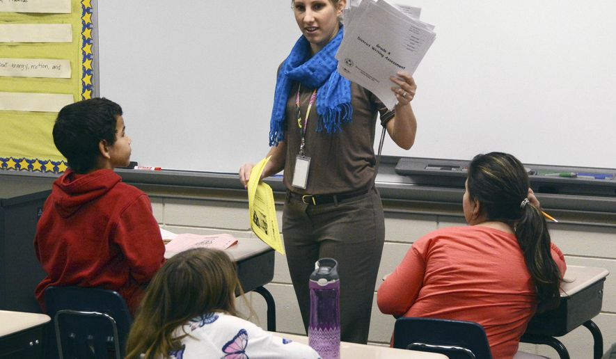 In this Feb. 4, 2016, photo, teacher Jessica Ries passes out writing assessment tests to her fourth-grade students at Hayward Elementary School in Sioux Falls, S.D. Ries is one of many teachers working two jobs in South Dakota, a state that ranks last in teacher pay. (AP Photo/Dirk Lammers)