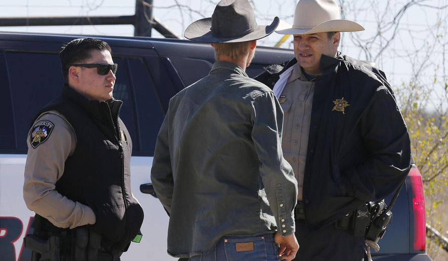 In this Saturday, Feb. 6, 2016 photo, Uvalde County Sheriffs Deputies talk with an individual while guarding the intersection to a neighborhood several miles outside of Uvalde after a standoff resulted in multiple deaths. The incident started on Friday.  (Kin Man Hui, San Antonio Express-News via AP) RUMBO DE SAN ANTONIO OUT; NO SALES; MANDATORY CREDIT