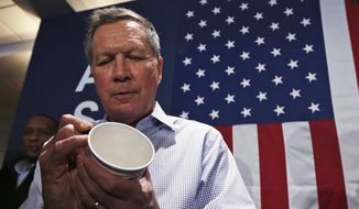 Republican presidential candidate, Ohio Gov. John Kasich signs an autograph on a paper cup for a guest during a campaign stop in Atkinson, N.H., Friday, Feb. 5, 2016. (AP Photo/Charles Krupa)