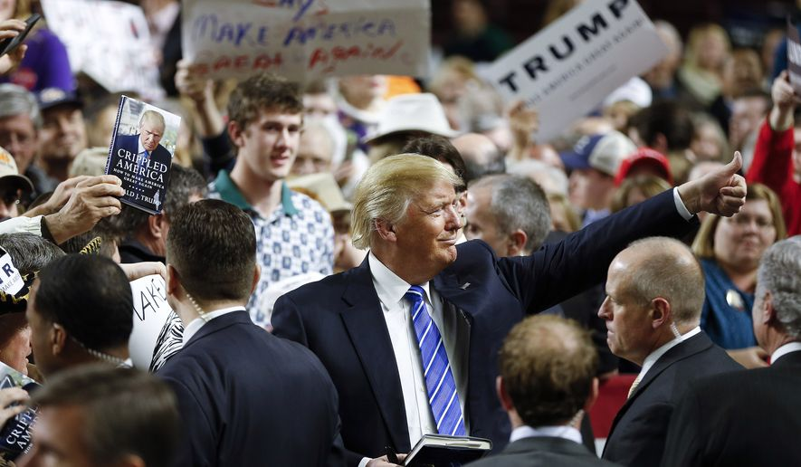 Republican presidential candidate Donald Trump gives a thumbs up to a supporter as he signs autograph after a rally Friday, Feb. 5, 2016, in Florence, S.C.  (AP Photo/John Bazemore)