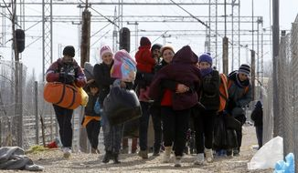 Refugees walk toward the border with Serbia from the transit center for refugees near northern Macedonian village of Tabanovce, Friday, Feb. 5, 2016. (AP Photo/Boris Grdanoski) ** FILE **