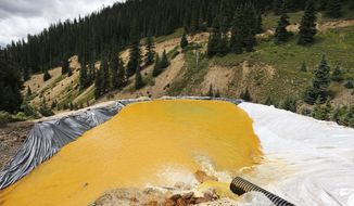 File--In this Wednesday, Aug. 12, 2015, file photograph, water flows through a series of retention ponds after a spill at the Gold King mine near Silverton, Colo. On Friday, Feb. 5, 2016, the Environmental Protection Agency said that the three million gallon spill from the gold mine may have dumped more than 880,000 pounds of metals into the Animas River. (AP Photo/Brennan Linsley, file)