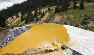 In this Wednesday, Aug. 12, 2015, file photograph, water flows through a series of retention ponds after a spill at the Gold King mine near Silverton, Colo. On Friday, Feb. 5, 2016, the Environmental Protection Agency said that the 3 million gallon spill from the gold mine may have dumped more than 880,000 pounds of metals into the Animas River. (AP Photo/Brennan Linsley, file)