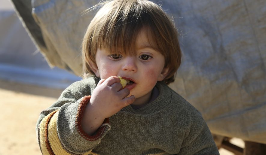 In this photo provided by Turkish Islamic aid group IHH, a displaced Syrian boy eats at a temporary refugee camp in northern Syria, near Bab al-Salameh border crossing with Turkey, Monday, Feb. 8, 2016. Turkey was under pressure from the EU to open its border to up to 35,000 Syrians who have massed along the frontier in the past few days fleeing an onslaught by government forces and intense Russian airstrikes in Aleppo. (IHH via AP)
