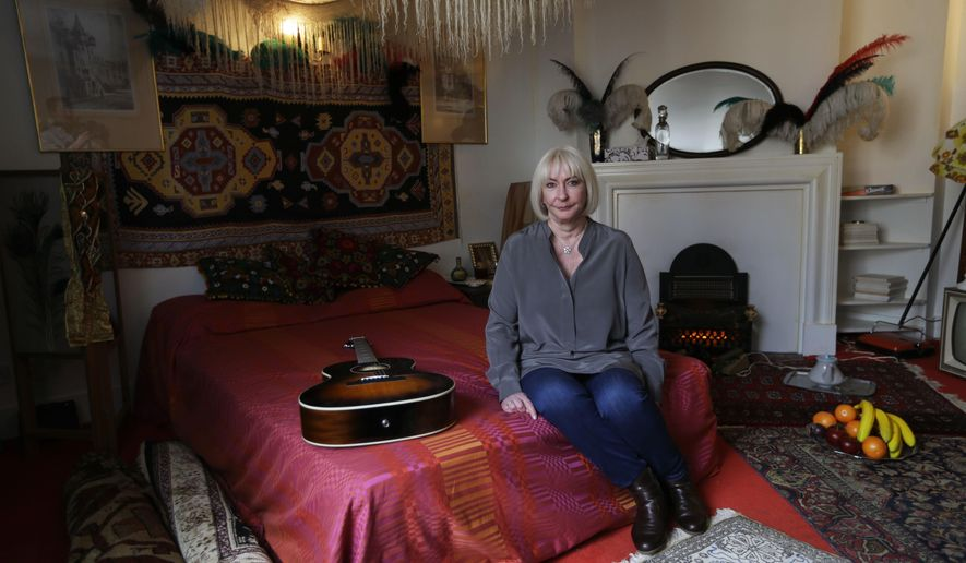 Kathy Etchingham, the former girlfriend of U.S. musician Jimi Hendrix, poses for photographers during a media preview in the bedroom of his former central London flat, at 23 Brook Street, London, Monday, Feb. 8, 2016. The flat where Hendrix lived in 1968 and 1969 opens to the public as a permanent exhibition on February 10 with the bedroom containing items sourced or crafted to replicate how it would have looked when he lived there. (AP Photo/Matt Dunham)