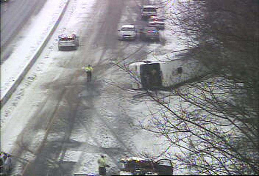 In this image from a Connecticut Department of Transportation traffic camera, a bus lies on the shoulder of northbound Interstate 95 Monday, Feb. 8, 2016, in Madison, Conn. The charter bus on its way from New York city to the Mohegan Sun casino crashed during a snowstorm, leaving at least 30 people injured, several critically, and closed the northbound side of the highway. (Connecticut Department of Transportation via AP)
