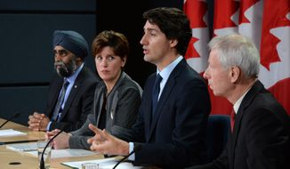 Canada Prime Minister Justin Trudeau answers a question as he is joined by Minister of National Defense Harjit Sajjan, left to right, Minister of International Development and La Francophonie Marie-Claude Bibeau and Minister of Foreign Affairs Stephane Dion during a news conference at the National Press Theatre in Ottawa on Monday, Feb. 8, 2016.  (Sean Kilpatrick/The Canadian Press via AP) MANDATORY CREDIT