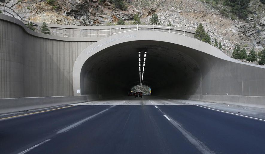 In this Saturday, Aug. 8, 2015, photograph taken near Idaho Springs, Colo., traffic flows through one of the newly-reconstructed twin tunnels along Interstate 70. Voter-sanctioned tax limits are threatening the state's growth, which depends on a functioning road system that has become crippled under the burden of an expanding population in recent years. (AP Photo/David Zalubowski)
