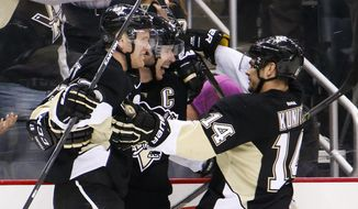 Pittsburgh Penguins' Sidney Crosby, center, celebrates his goal with teammates Patric Hornqvist, left, and Chris Kunitz (14) during the second period of an NHL hockey game against the Anaheim Ducks in Pittsburgh, Monday, Feb. 8, 2016. (AP Photo/Gene J. Puskar)