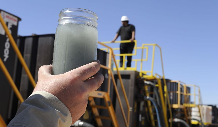 File-This Sept. 24, 2013, file photo shows a jar holding waste water from hydraulic fracturing is held up to the light at a recycling site in Midland, Texas. Texas was among the first states in the country in 2011 to pass a hydraulic fracturing disclosure law, which supporters called a popular and landmark piece of legislation designed to improve transparency. Environmentalists complained, though, that the Texas legislation gave industry-wide latitude in deciding what ingredients to make public. (AP Photo/Pat Sullivan, File)