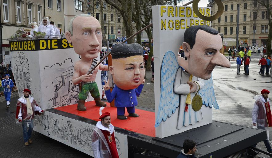 A carnival float depicting from left:  Russian president Vladimir Putin, North Korean  leader Kim Jong-un and Syrian president Bashar al-Assad as  Angels of Peace  during the traditional carnival parade in Cologne, western Germany, Monday, Feb. 8, 2016. Many carnival parades in Germany were cancelled because of heavy stormy weather. The foolish street spectacle in Cologne, normally watched by hundreds of thousands of people, is the highlight in Germany's carnival season on Rose Monday.  Words on  the poster near  the Assad  doll reads:  Nobel Peace Prize. (AP Photo/Martin Meissner)