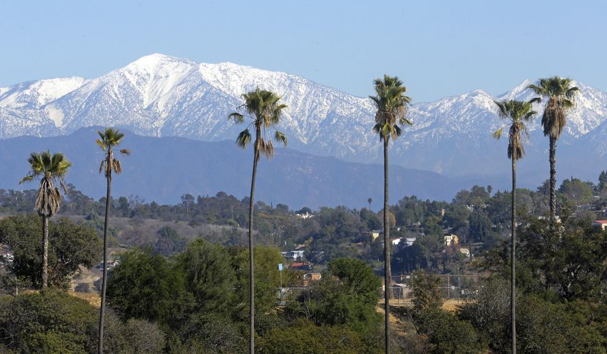 FILE - This Jan. 12, 2016 file photo shows the snow-capped San Gabriel Mountains, with Mount Baldy the highest peak at the left, seen from Chinatown near downtown Los Angeles. Authorities have closed trails at Baldy following the death of the second hiker in a week. San Bernardino County sheriff's officials say 47-year-old Dong Xing Liu died Saturday, Feb. 6, 2016, after he slipped and fell in the Icehouse Saddle area.(AP Photo/Nick Ut, File)
