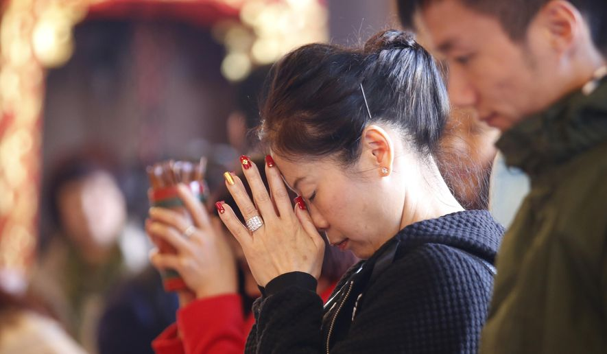 Chinese visitors pray during the celebration of the Lunar New Year at a temple in Hong Kong, Monday, Feb. 8, 2016. The celebration marks the Year of the Monkey in the Chinese calendar. (AP Photo/Kin Cheung)