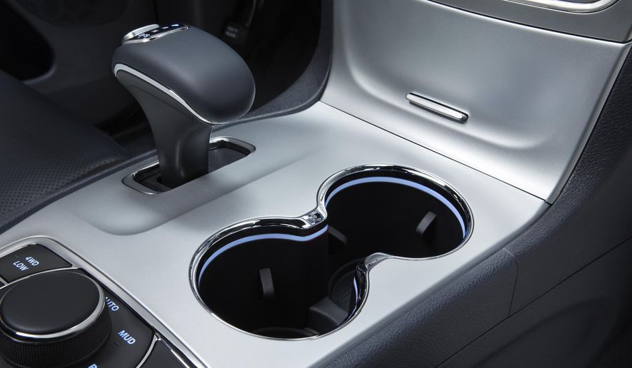 This photo provided by Fiat Chrysler Automobiles shows the interior of a 2014 Jeep Grand Cherokee Overland. U.S. auto safety investigators have determined that electronic gear shifters, like the one at upper left, in some newer Fiat Chrysler SUVs and cars are so confusing that drivers have exited the vehicles while they are in gear, causing 121 crashes and 30 injuries. The National Highway Traffic Safety Administration has doubled the number of vehicles in the investigation to more than 856,000. But it stopped short of calling for a recall. The probe now covers 2014 and 2015 Jeep Grand Cherokees and 2012 through 2014 Dodge Charger and Chrysler 300 sedans with 3.6-liter V6 engines. (Fiat Chrysler Automobiles via AP)