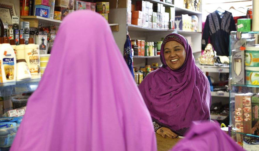 "In this Tuesday, Jan. 26, 2016 photo, Shukri Abasheikh, owner of Mogadishu Store, speaks with a customer in Lewiston, Maine. ""When Somalis came in, Lewiston people, Maine people, they think they need welfare but we don't need welfare. We need jobs. We need peace. We need education,"" said Abasheikh, who worked as a janitor before achieving her dream of running her own business. (AP Photo/Robert F. Bukaty)"