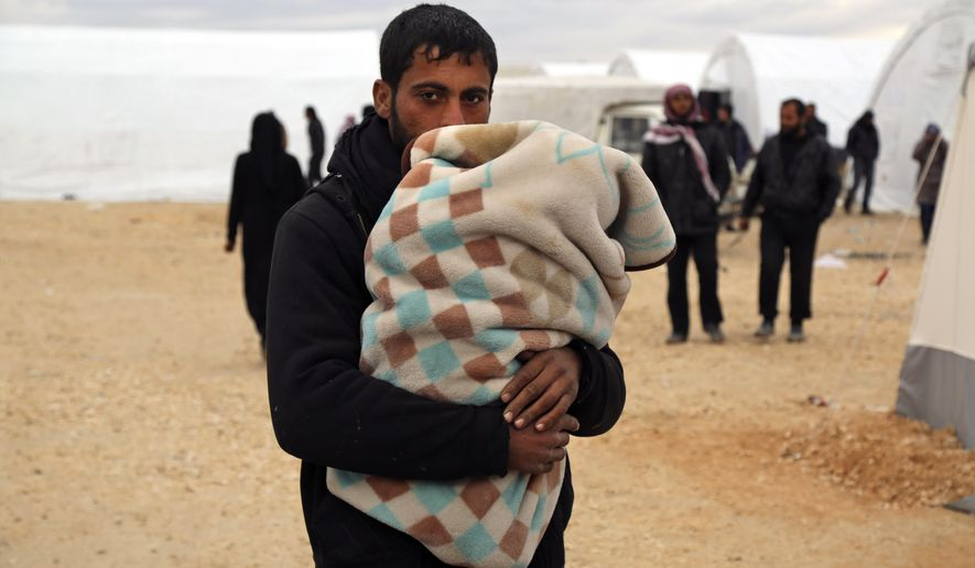 In this photo provided by Turkish Islamic aid group IHH, Syrians gather at a temporary refugee camp for displaced Syrians in northern Syria, near Bab al-Salameh border crossing with Turkey, Sunday, Feb. 7, 2016. Turkey is facing mounting pressure to open its border as tens of thousands of Syrian fleeing a government onslaught and intense Russian airstrikes arrived at the frontier. (IHH via AP)