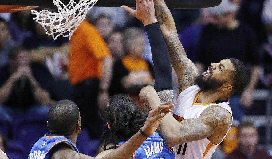 Phoenix Suns' Markieff Morris, right, gets fouled by Oklahoma City Thunder's Steven Adams, center, of New Zealand, as he goes up for a shot while Thunder's Kevin Durant, left, watches during the first half of an NBA basketball game Monday, Feb. 8, 2016, in Phoenix. (AP Photo/Ross D. Franklin)