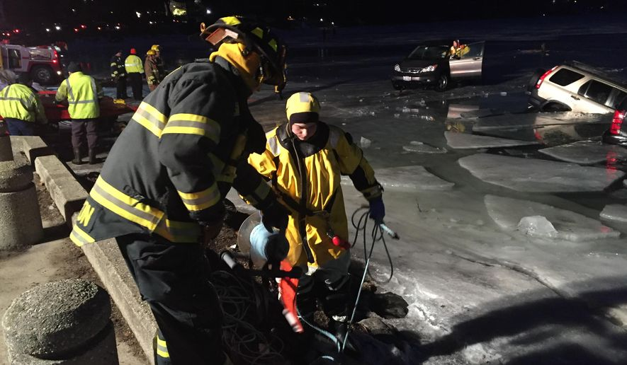 Emergency personnel cut through the ice as multiple vehicles fall through on Geneva Lake in Lake Geneva, Wis., on Satrurday, Feb. 6, 2016.  The cars were parked on the ice of lake when they began breaking through Saturday. Officers arrived and found 15 vehicles were partially submerged in the water. Tow companies removed the cars. No one was hurt. (Daniel Gaitan/The Kenosha News via AP) MANDATORY CREDIT