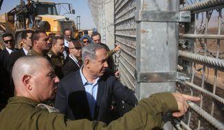 Israeli Prime Minister Benjamin Netanyahu and IDF Chief of Staff Gadi Eizenkott, left, visit the construction work on the fence between Israel and Jordan Tuesday, Feb. 9, 2016.  (Marc Israel Sellem, Jerusalem Post, Pool via AP)
