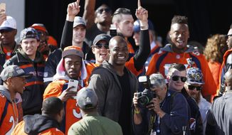 Denver Broncos outside linebacker DeMarcus Ware, center, smiles while surrounded by teammates at a rally following a parade through downtown Tuesday, Feb. 9, 2016 in Denver. Fans crowded into Denver's downtown to salute the Broncos for the team's victory over the Carolina Panthers in Super Bowl 50. (AP Photo/David Zalubowski)